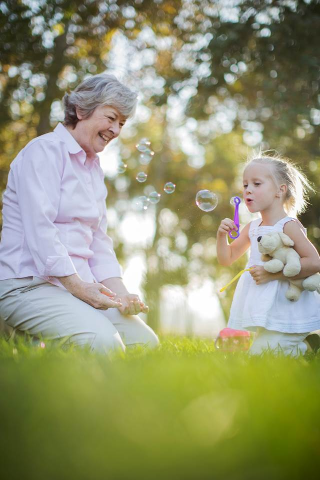 Grandmother And Granddaughter Playing With Bubbles