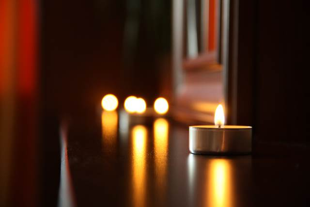 Candles Lit On Wooden Shelving