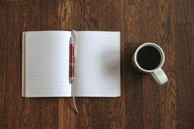 Notebook And Coffee On A Wooden Desk