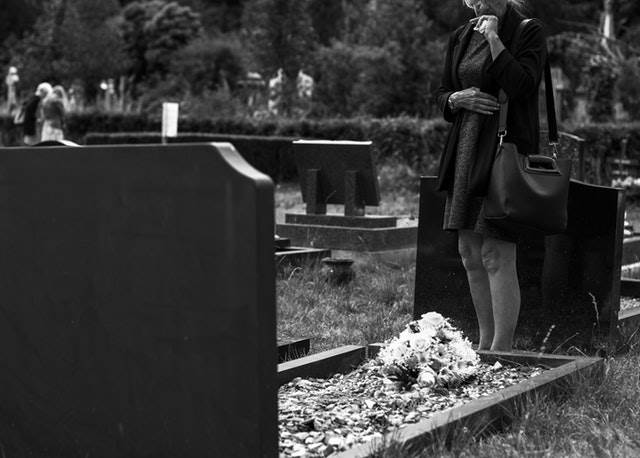 Woman Grieving At A Grave