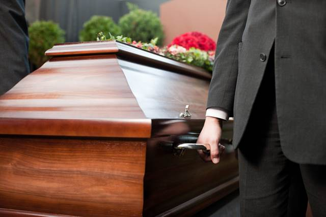 Men Carrying Coffin At Funeral